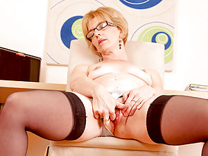Hot older business woman in glasses fingers her pussy