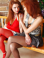 Redhead in bright red nylons takes turns with a girl riding a strap-on cock